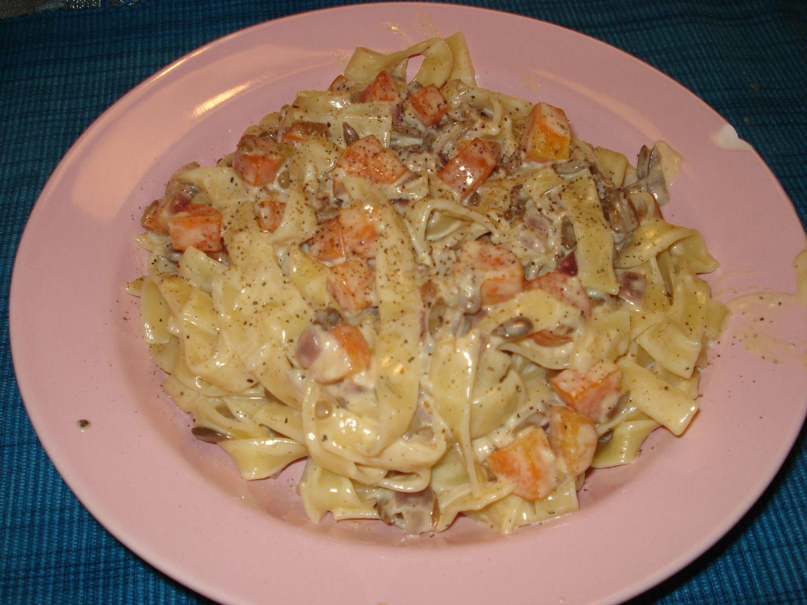 Pasta in a cheese sauce with carrots and sunflower seeds