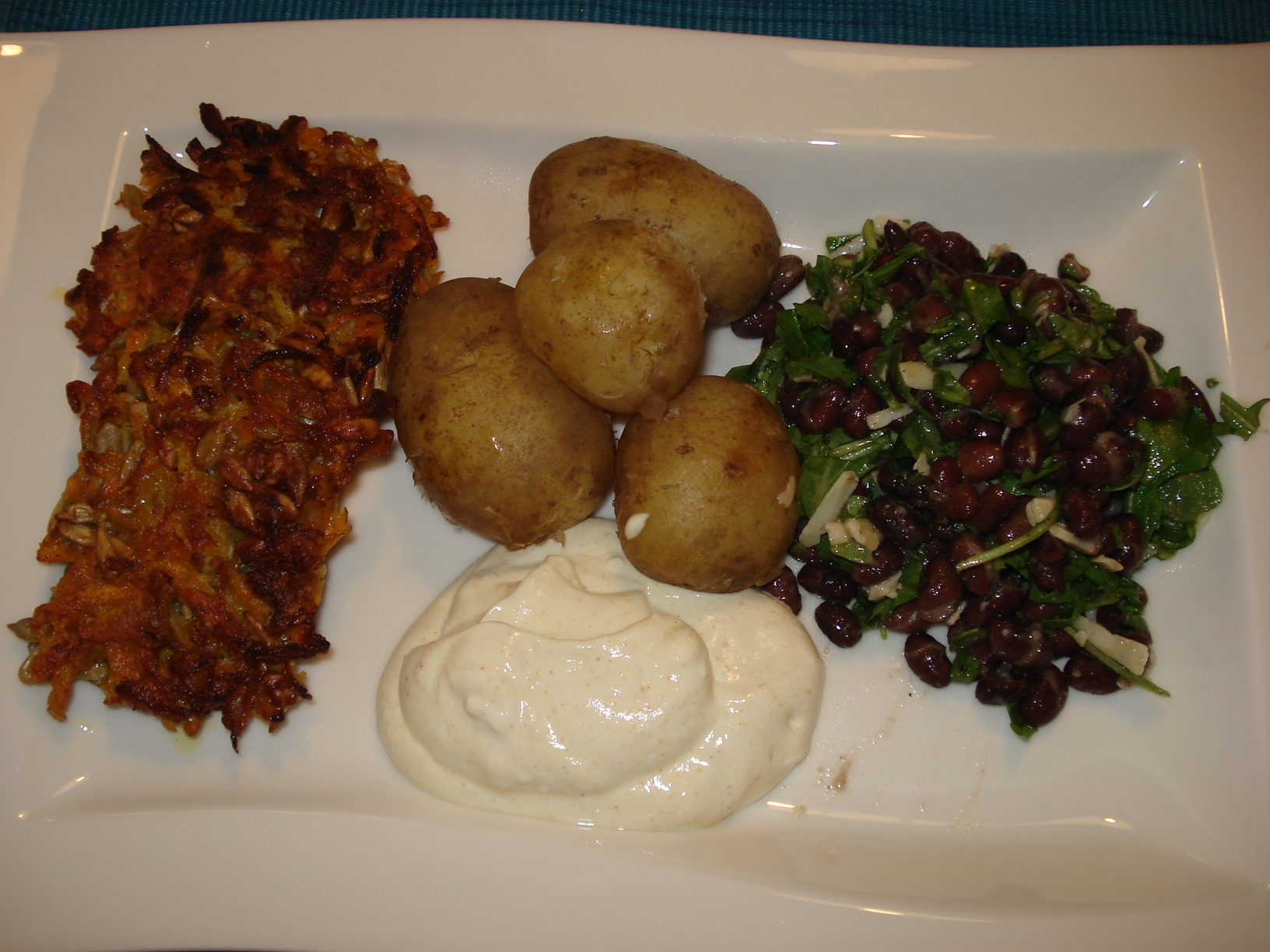 Carrot and sunflower seed patties with potatoes, curry yoghurt and bean salad