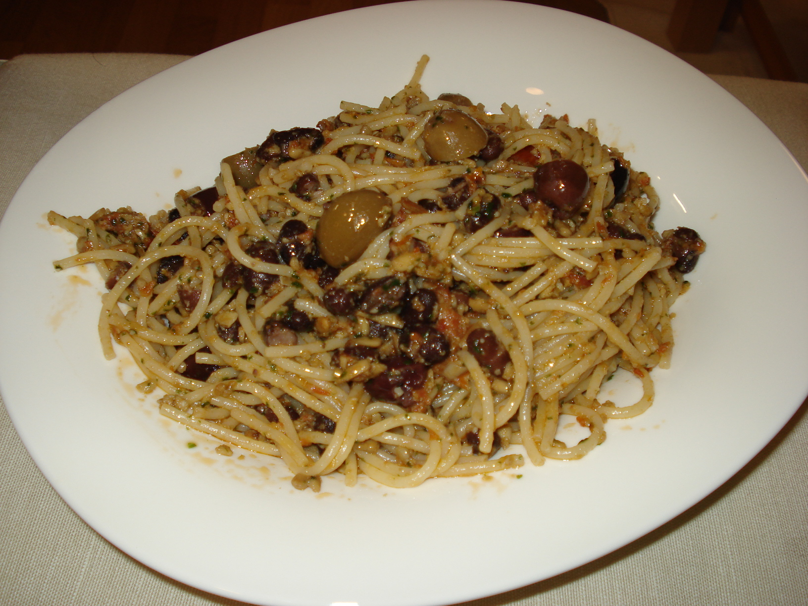 Spaghetti with red sunflower seed pesto, olives and black beans