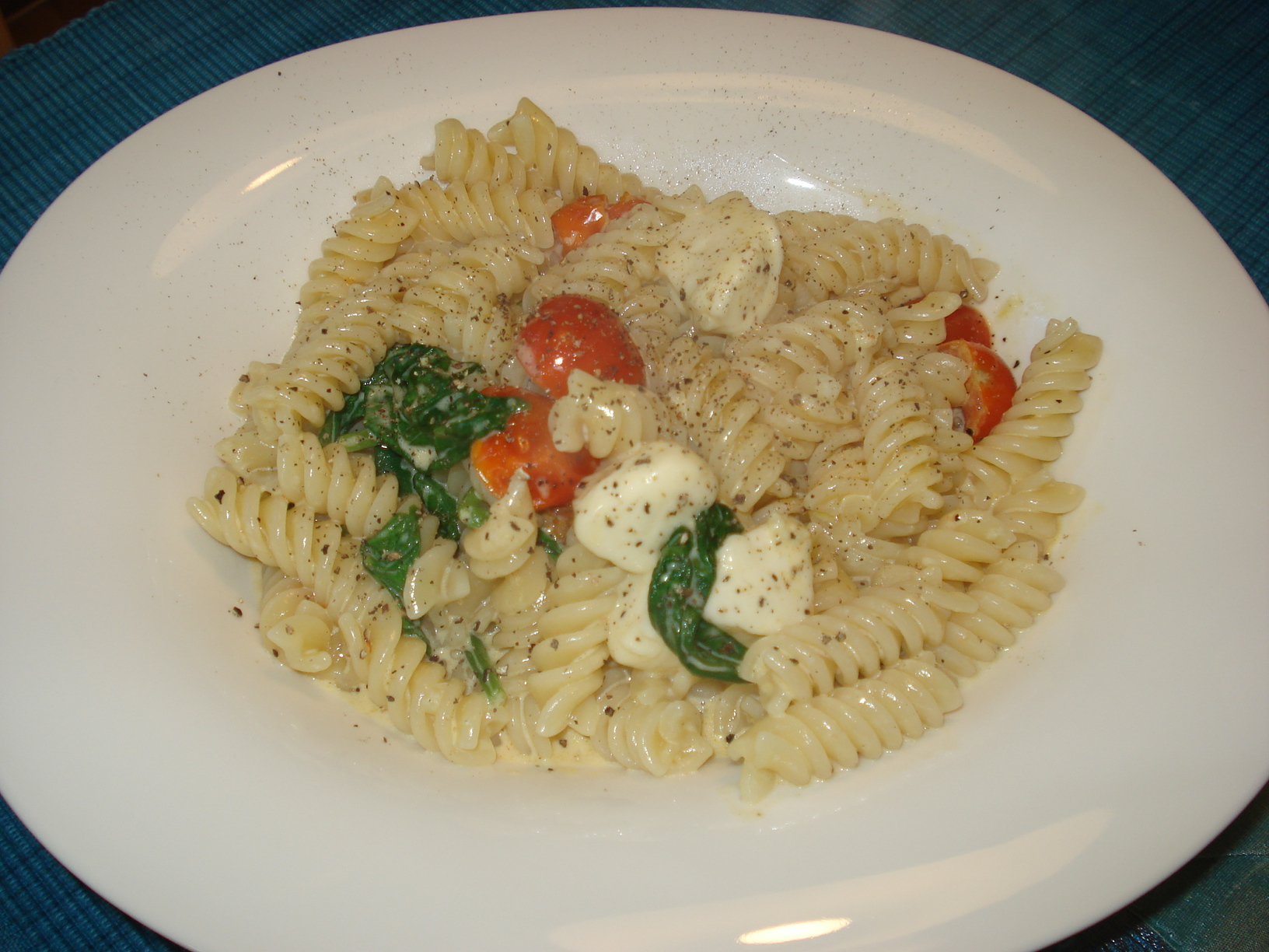 Pasta with cream, mozzarella, tomato and spinach