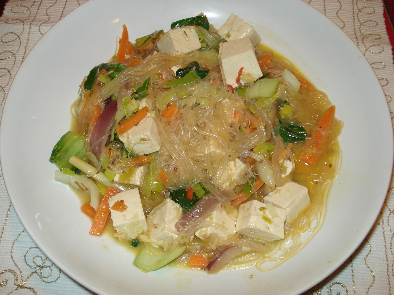 Wok with tofu, noodles and vegetables in a ginger and coconut sauce